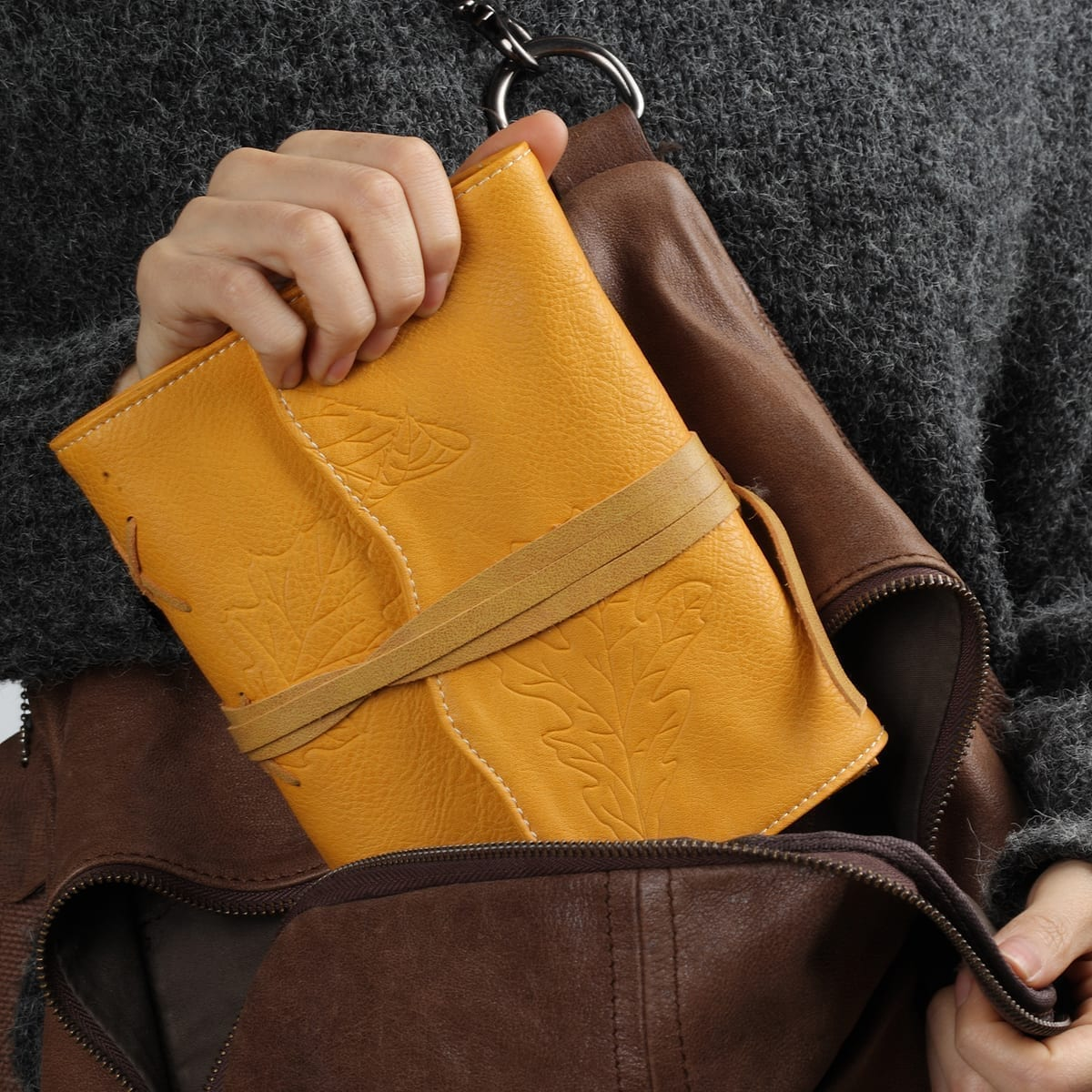 putting yellow leather journal in a backpack